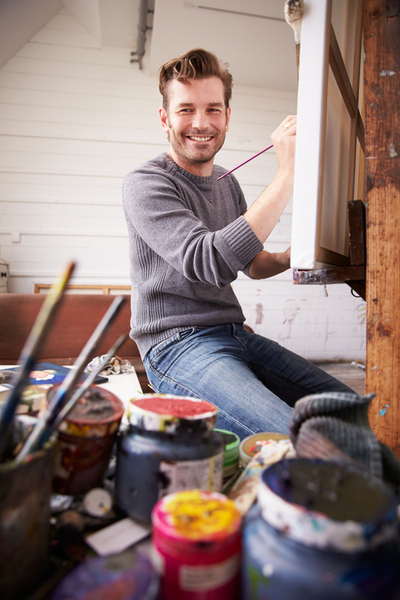 Portrait Of Male Artist Working On Painting In Studio