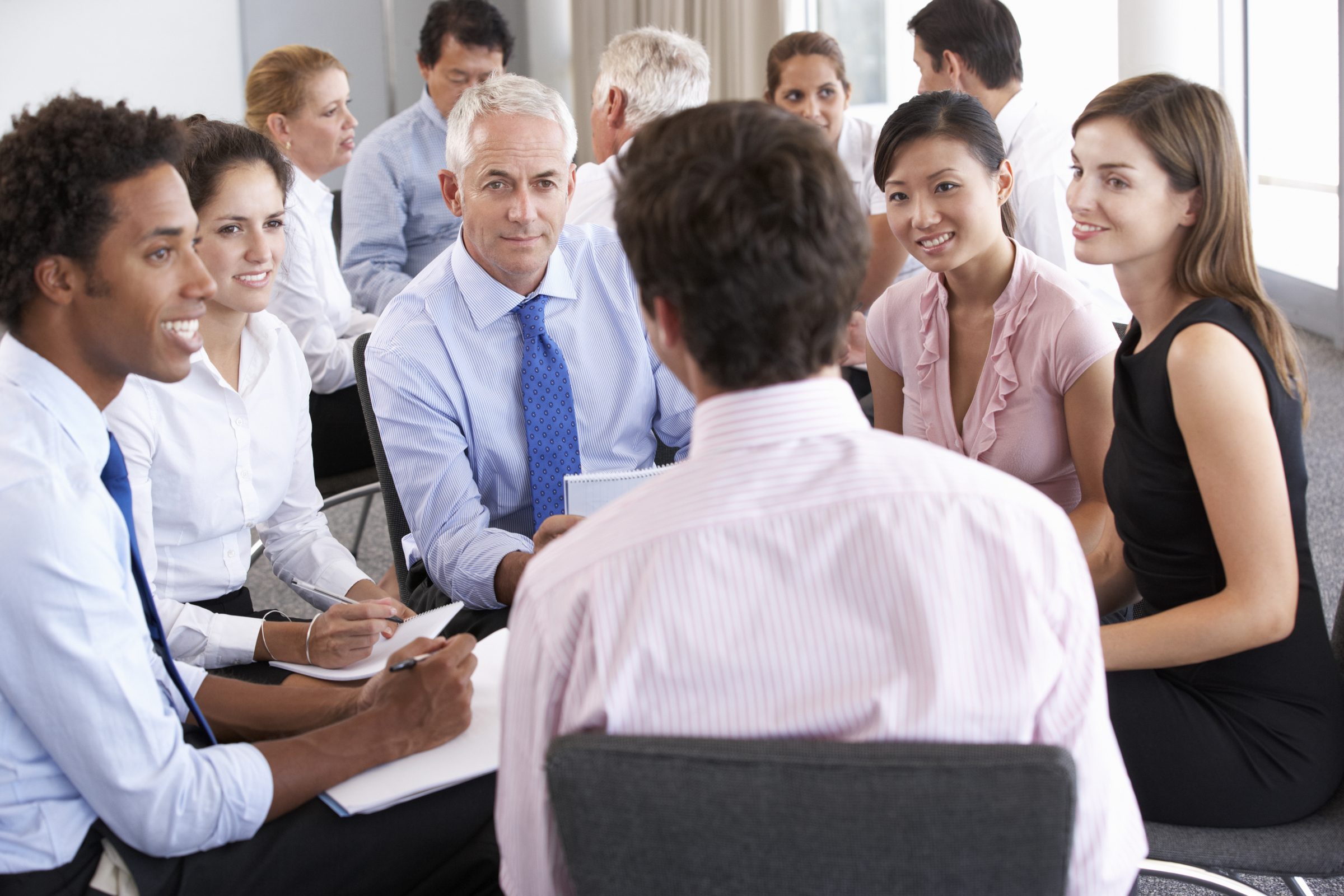 Businesspeople Seated In Circle At Company Seminar